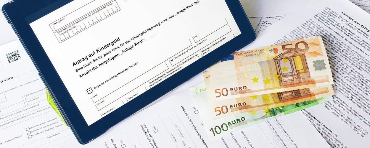 Kindergeld Antrag auf Tablet mit Geldscheinen